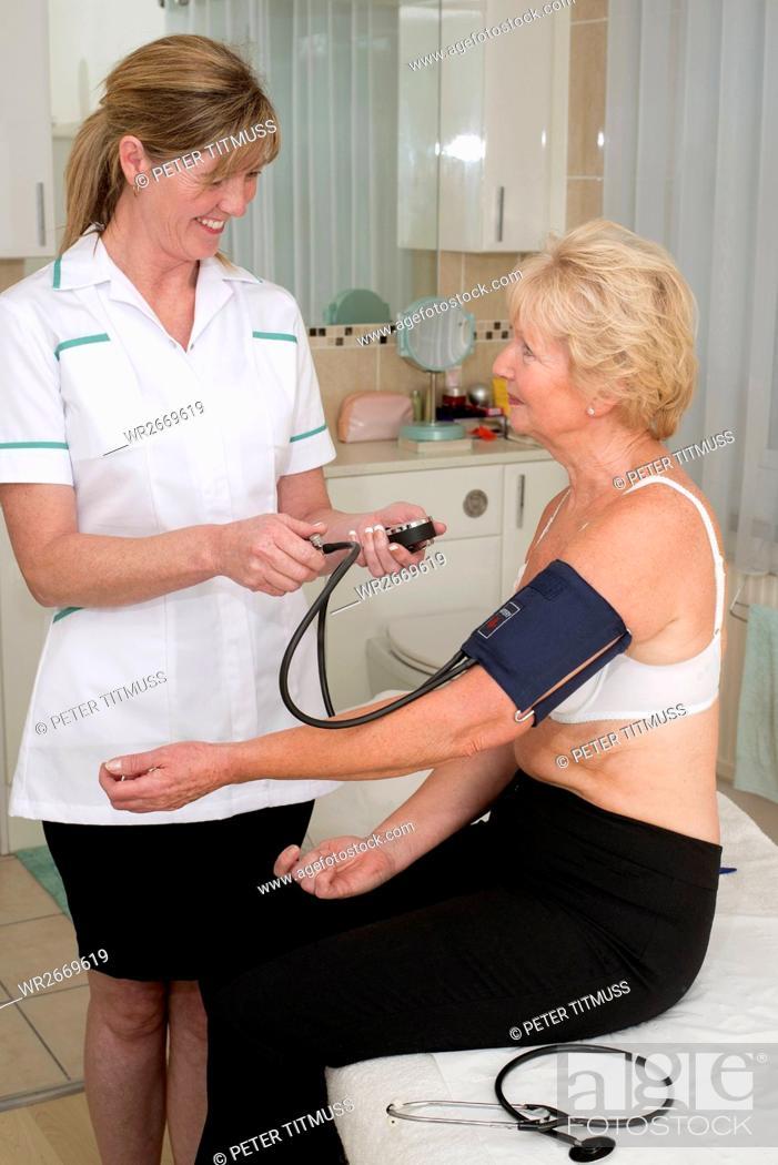 Stock Photo: Nurse checking elderly woman's blood pressure.