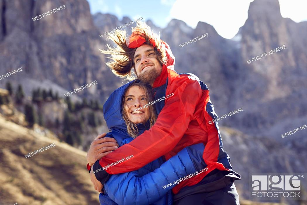 Stock Photo: Happy young couple hugging in windy mountains.