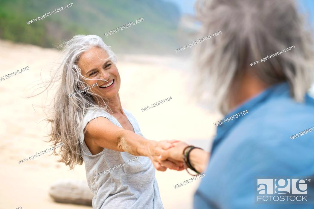 Stock Photo: Handsome senior couple dancing on the beach.