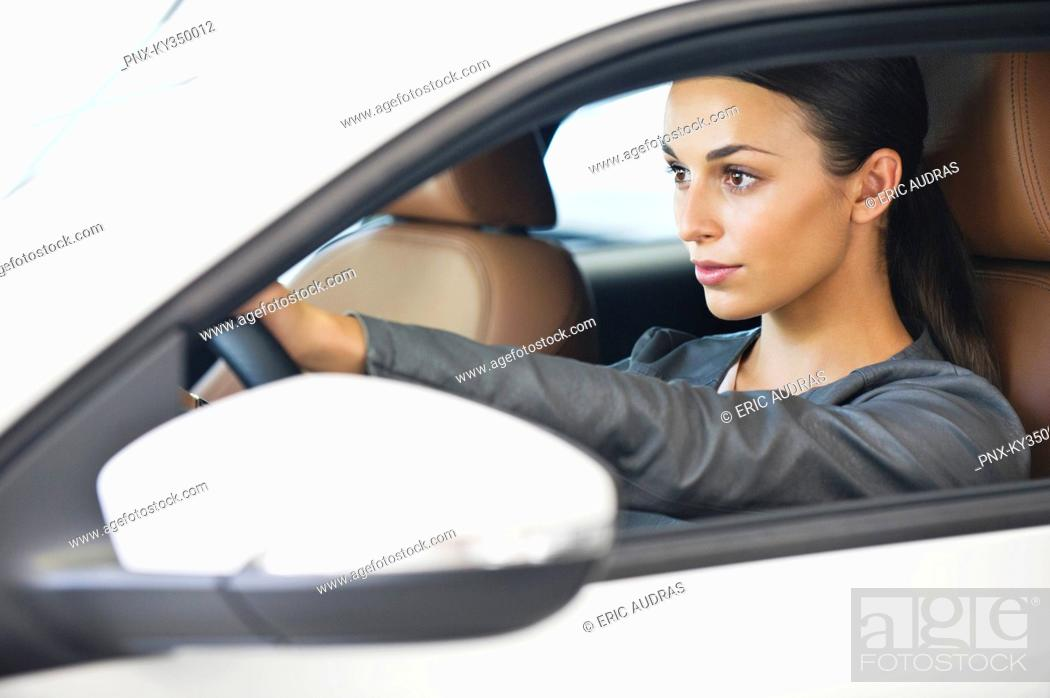 Stock Photo: Beautiful young woman taking a test drive.