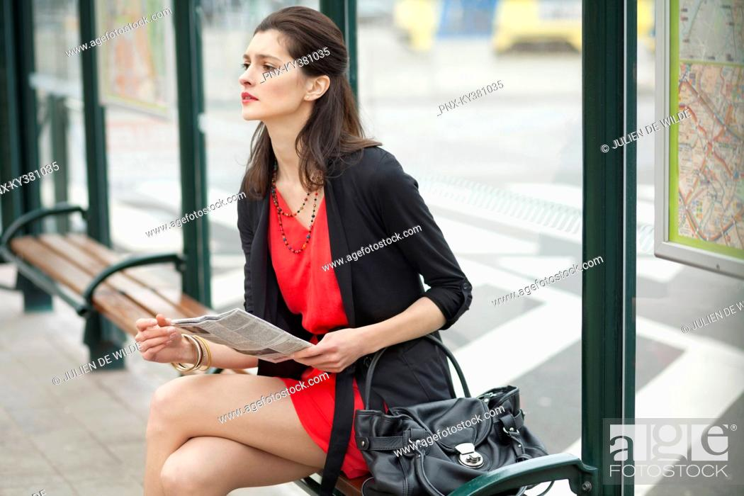 Stock Photo: Woman sitting at a bus stop and holding a newspaper.