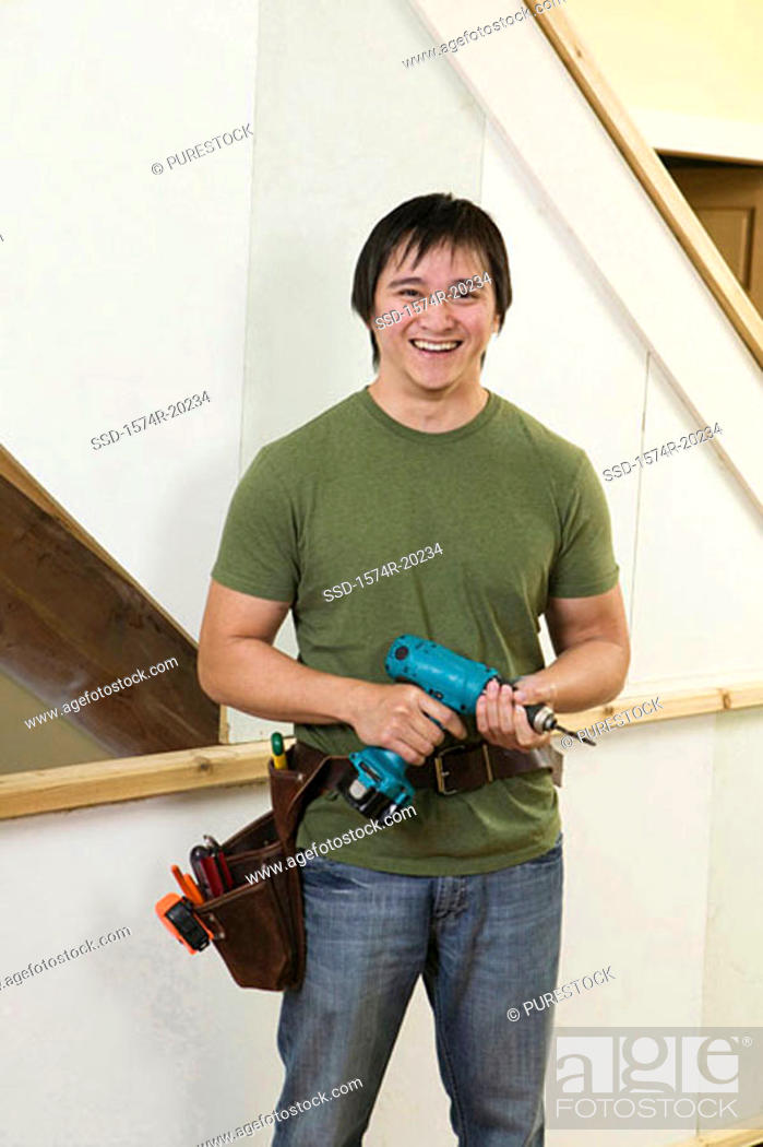 Stock Photo: Portrait of a young man holding a drill smiling.