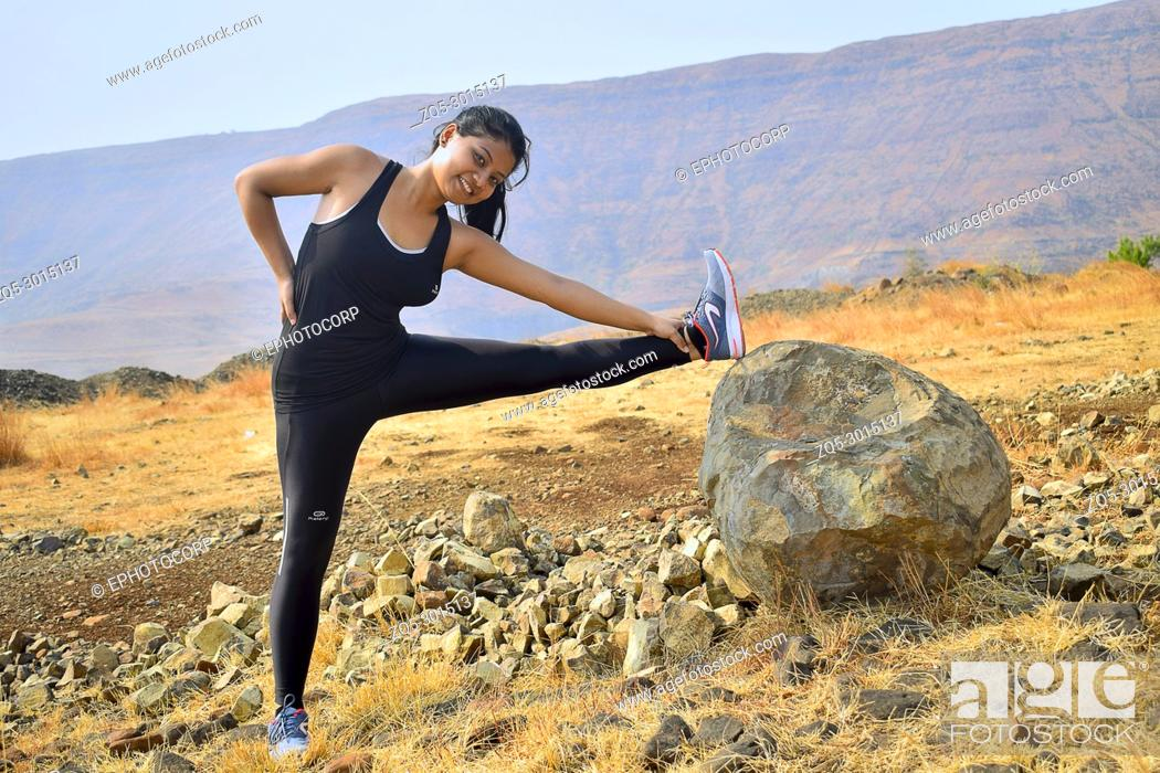 Stock Photo: Young Indian girl doing fitness exercise. Mountain backdrop, Pune, Maharashtra.