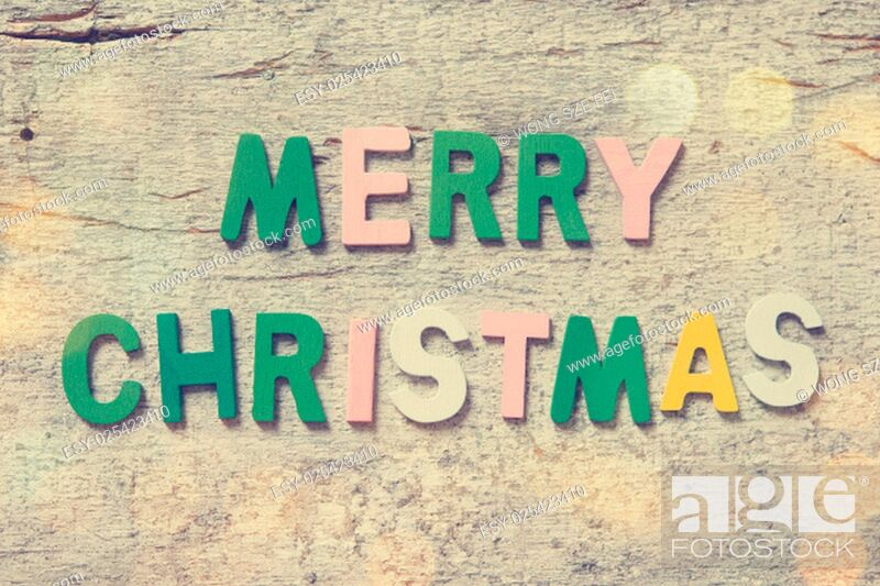 """Stock Photo: The colorful words """"""""MERRY CHRISTMAS"""""""" made with wooden letters on old wooden board."""