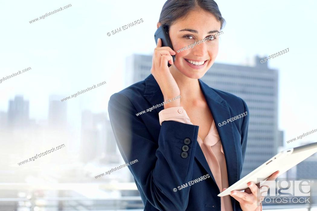 Stock Photo: Portrait of smiling woman holding digital tablet and talking on cell phone.