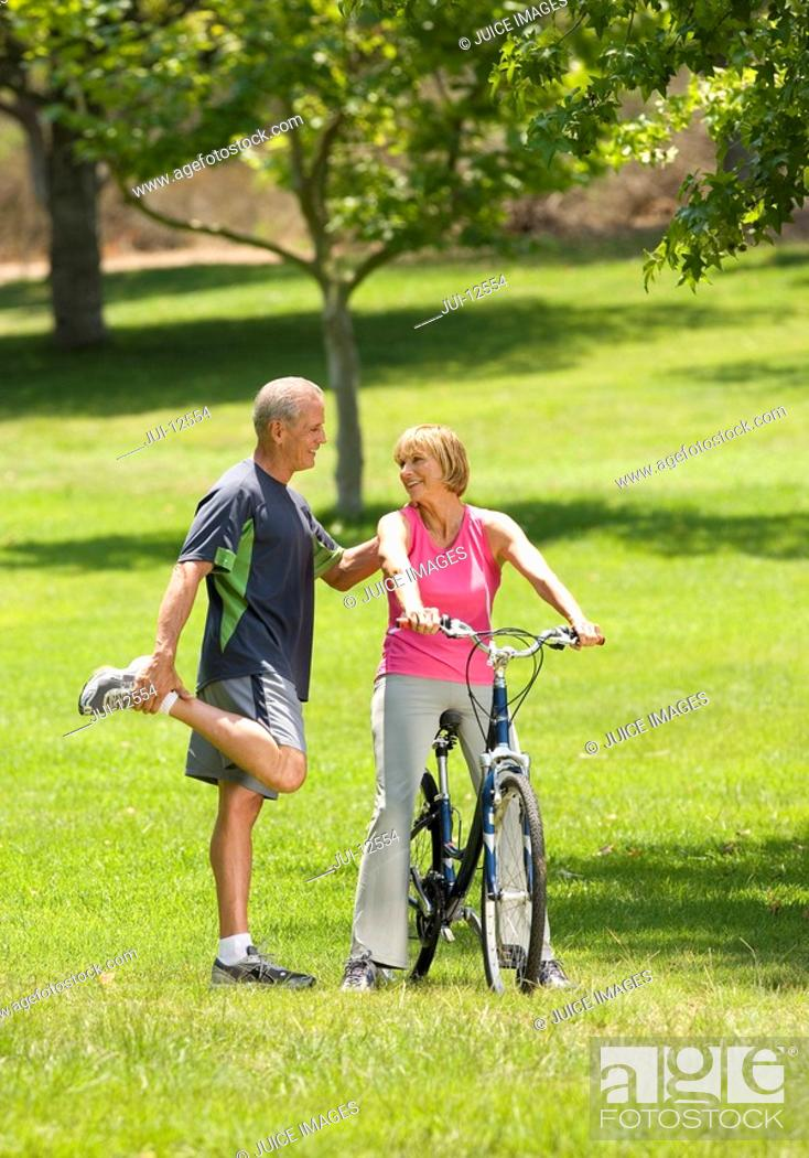Stock Photo: Mature man stretching with hand on shoulder of woman on bicycle, smiling.