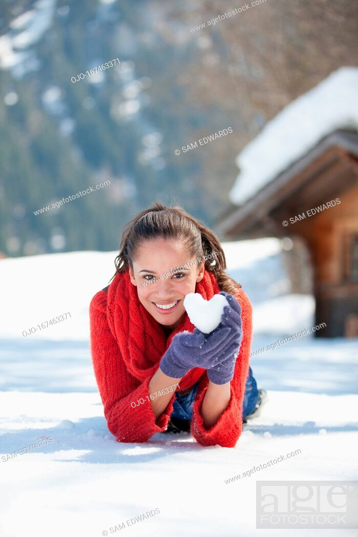 Stock Photo: Portrait of smiling woman holding heart-shaped snowball.