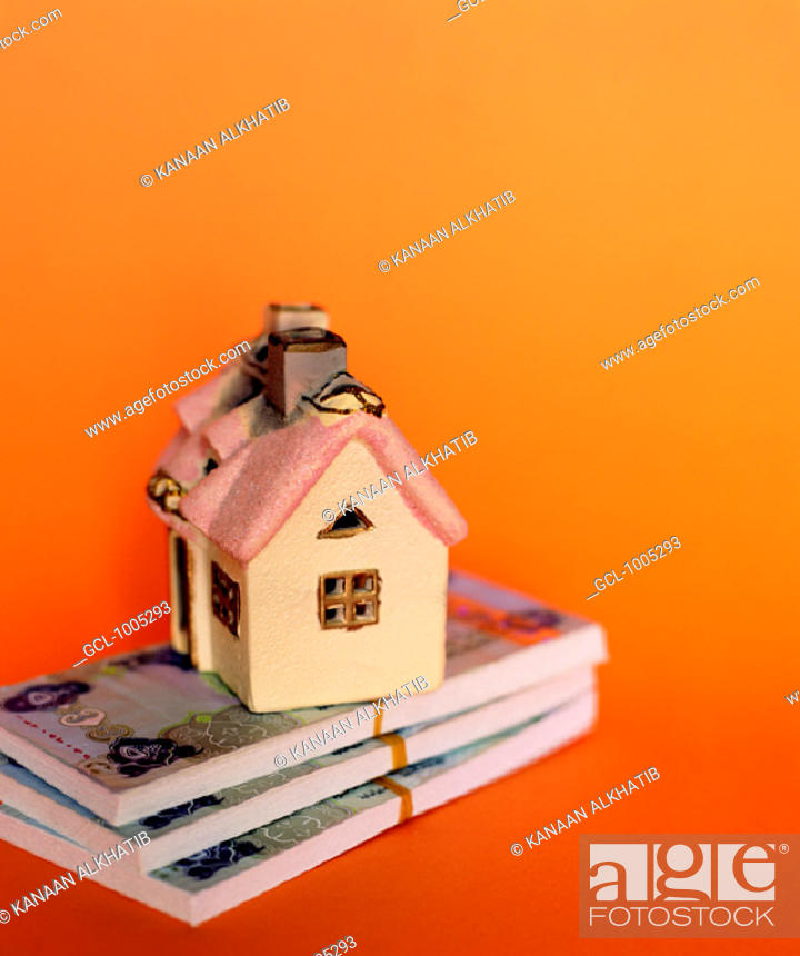 Stock Photo: Toy house on top of piles of UAE money.