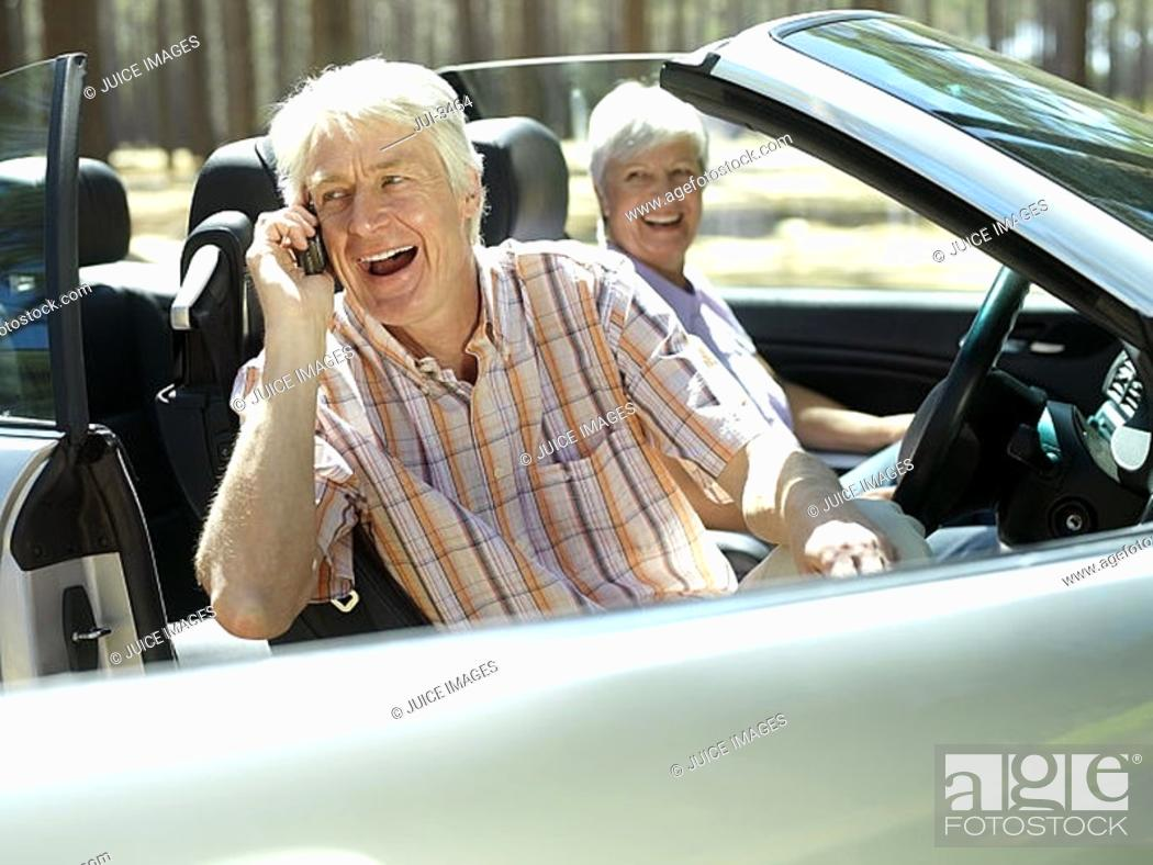 Stock Photo: Senior couple sitting in convertible car, man using mobile phone, smiling, side view.