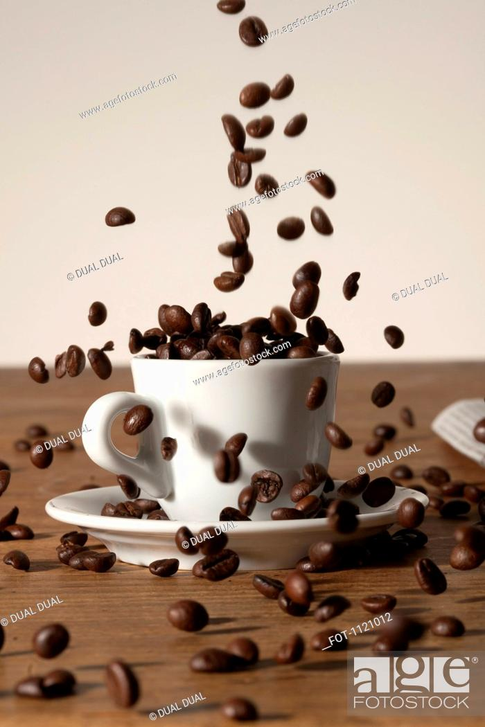 Stock Photo: Coffee beans being poured into a cup.