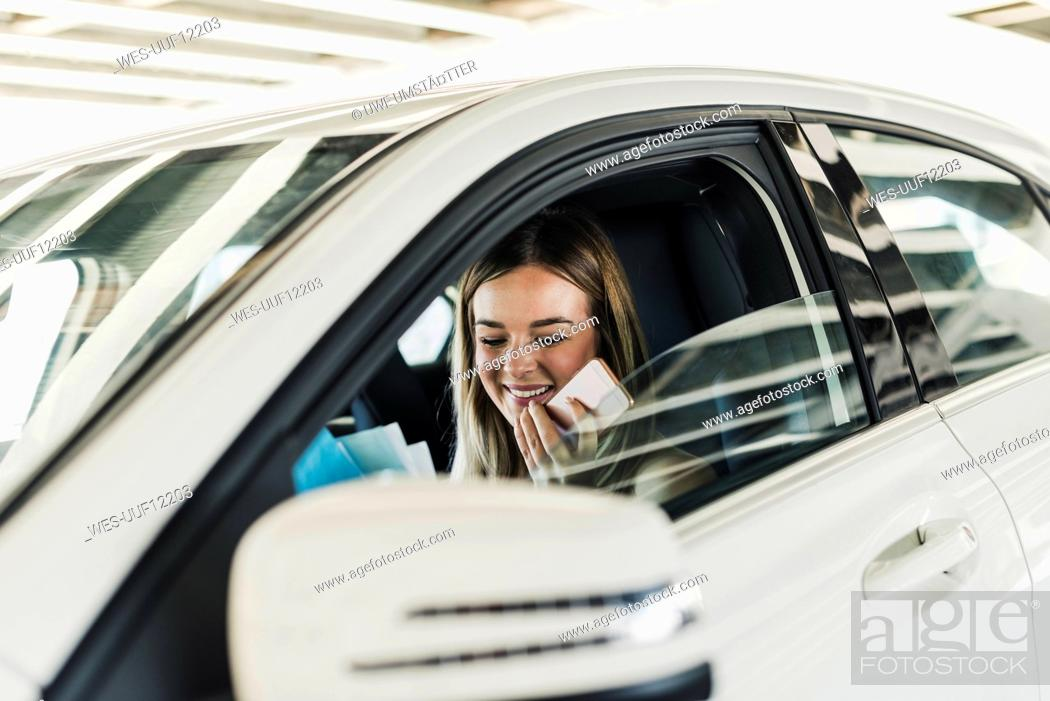 Imagen: Smiling young woman with cell phone in car.