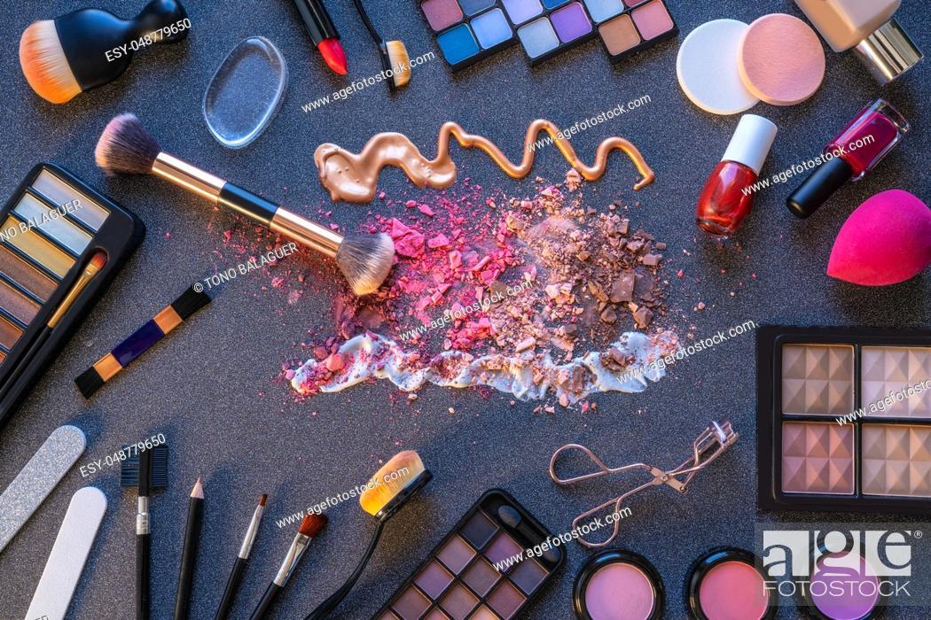 Stock Photo: Cosmetics makeup lipstick eye shadows arrangement on glitter dark gray table.