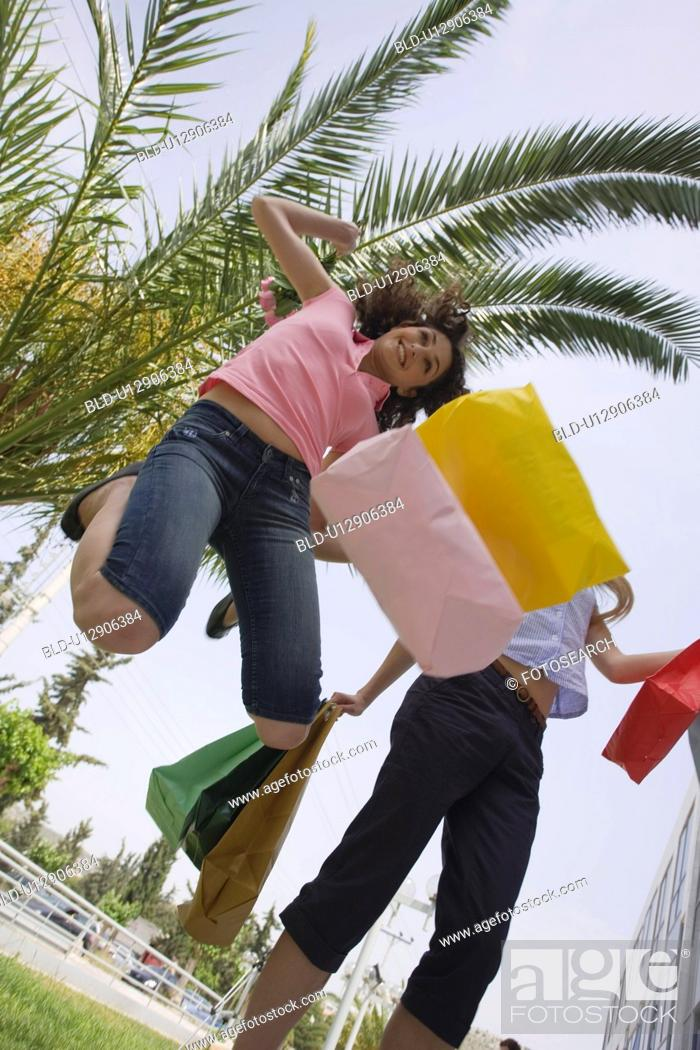 Stock Photo: Women with shopping bags jumping.