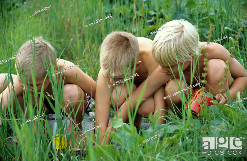 Stock Photo: Three children, boys, 5-10 years old, playing in the garden at the water.