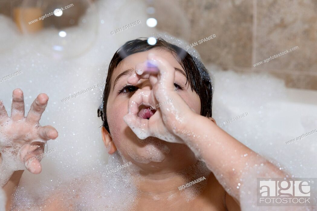 Stock Photo: Young boy blowing bubbles in bubble bath.