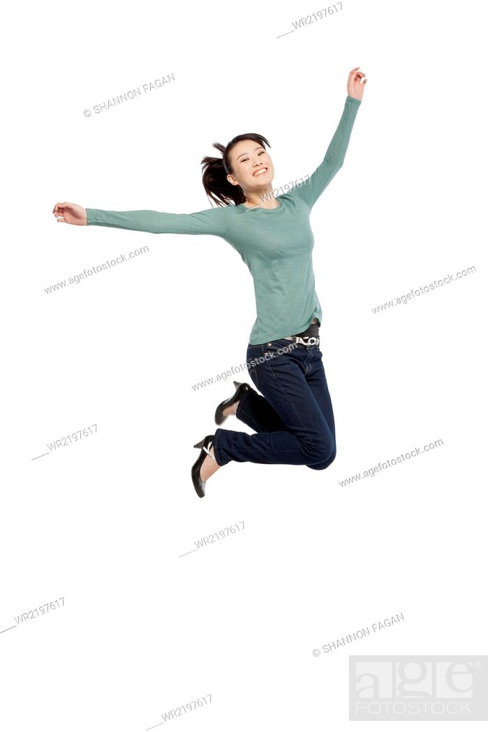 Stock Photo: Portrait of an excited young woman mid-air.