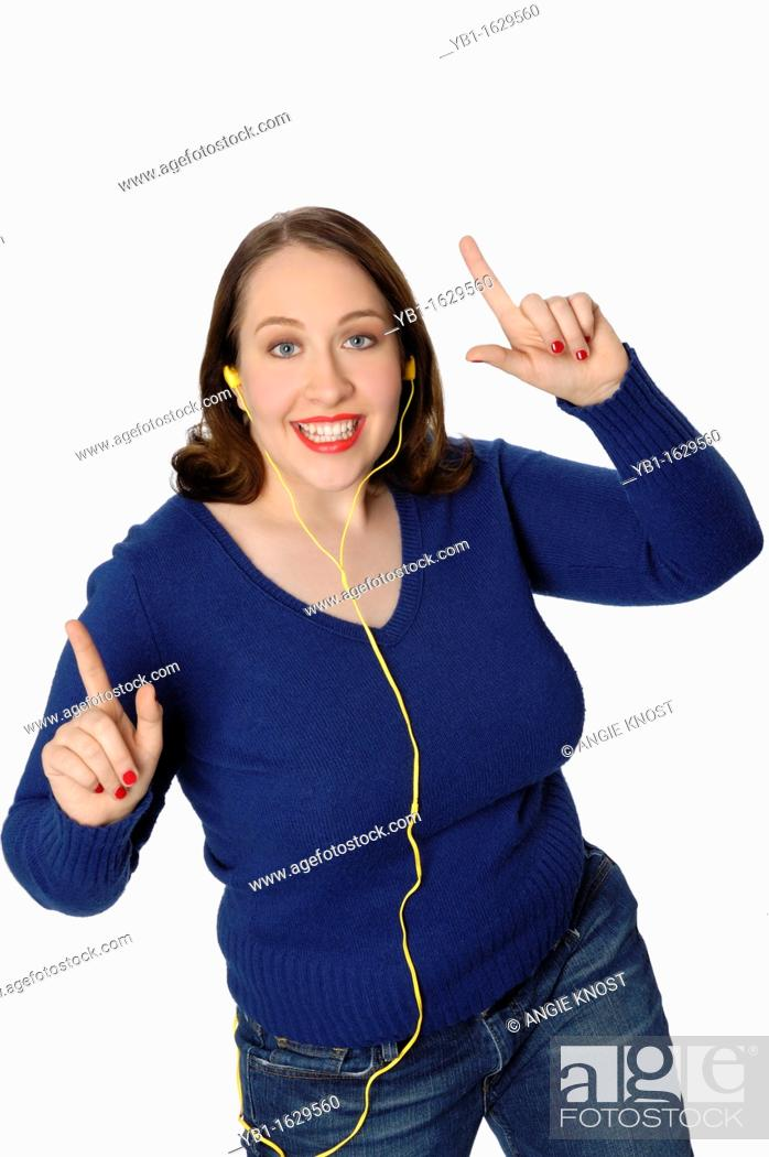 Stock Photo: Young lively woman listening to music in an MP3 player and dancing a lively dance.