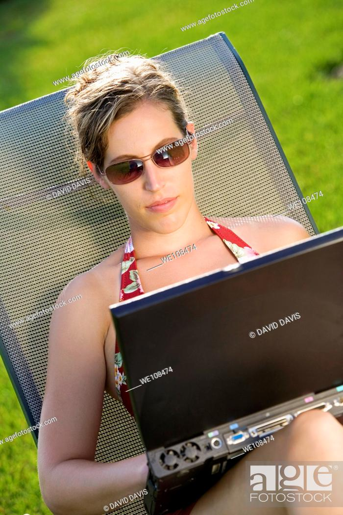Stock Photo: Woman in mid 20s sunbathing and working on a laptop computer.