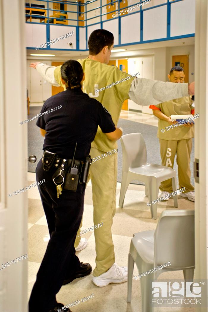 Stock Photo: A male prisoner is searched by a female corrections officer in the Santa Ana, CA  city jail  Note day room in background.