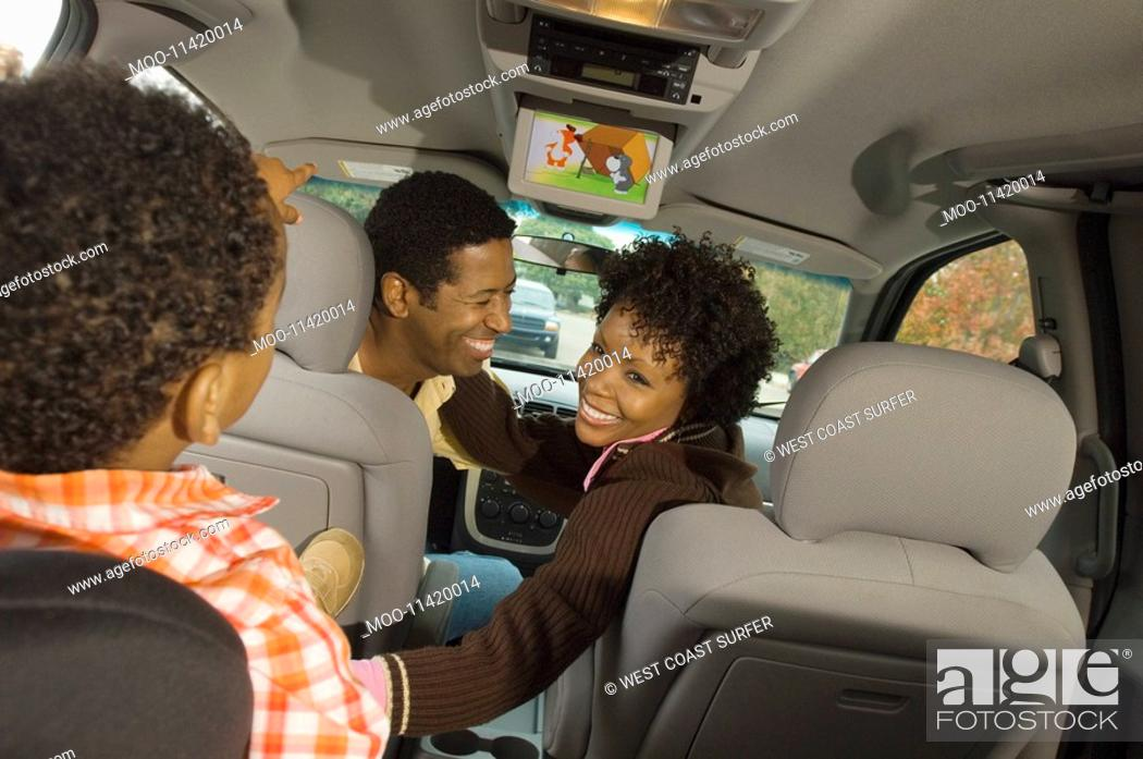Stock Photo: Couple smiling at young son in car.