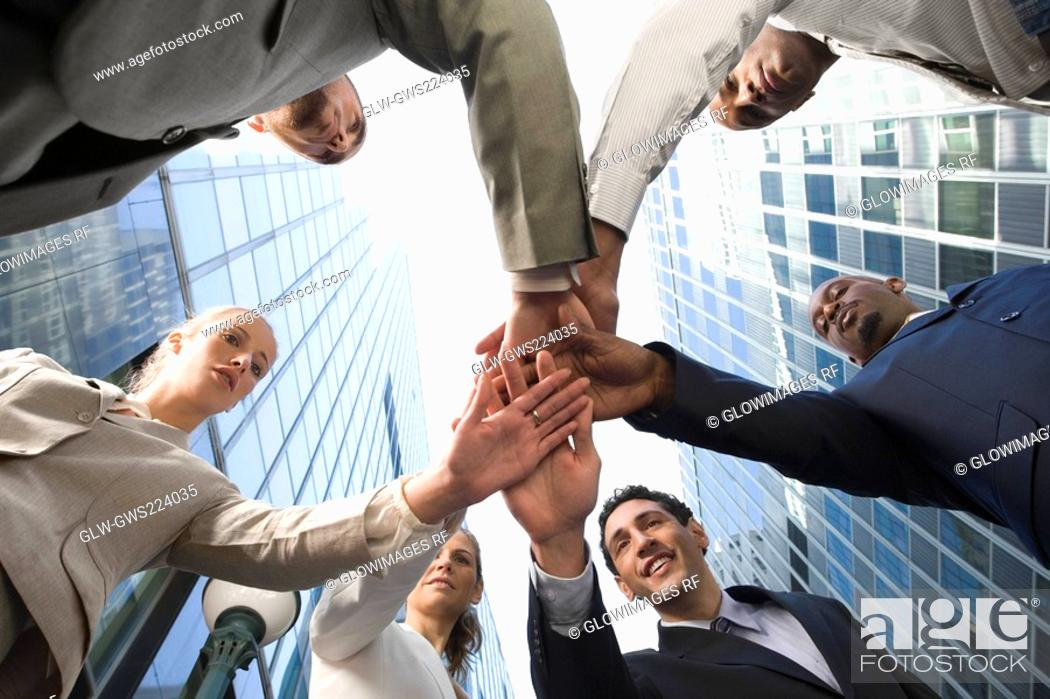 Stock Photo: Low angle view of business executives stacking hands.