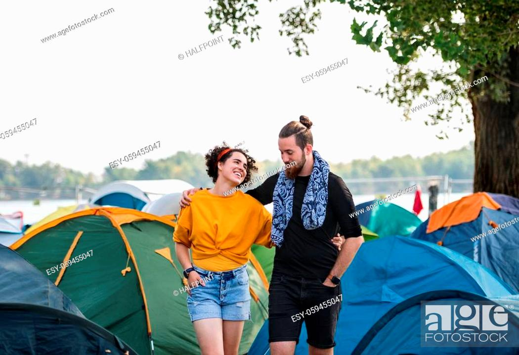 Imagen: Young couple on vacation holiday, walking arm in arm among tents.