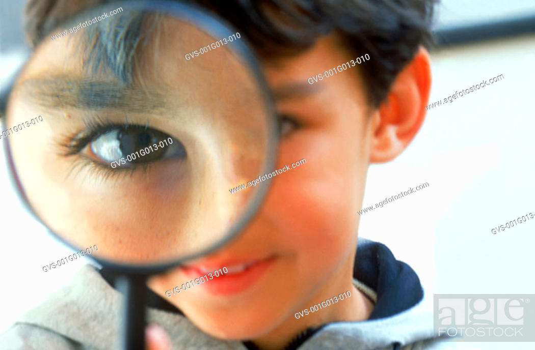 Stock Photo: A boy looking through a magnifying glass.