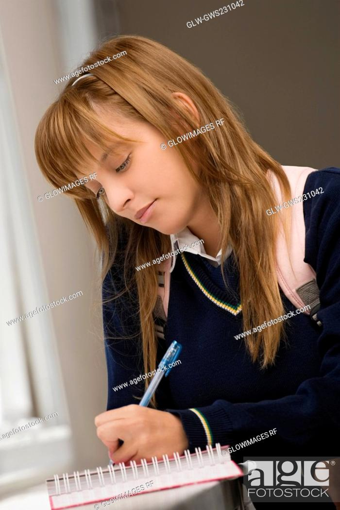 Stock Photo: Close-up of a teenage girl writing in a spiral notebook.