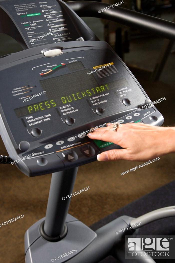 Stock Photo: Prime adult Caucasian female setting up elliptical machine at gym.