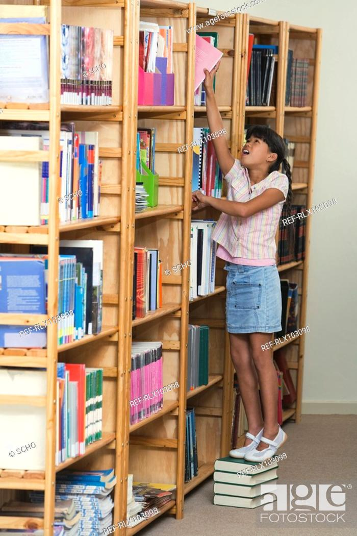 Stock Photo: Schoolgirl 10-13 standing in library stretching to put book in bookshelf.