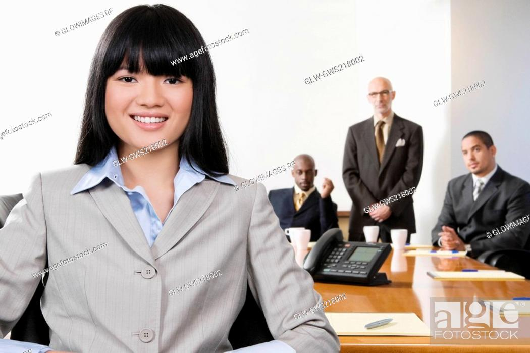 Stock Photo: Portrait of a businesswoman smiling with her colleagues in the background.