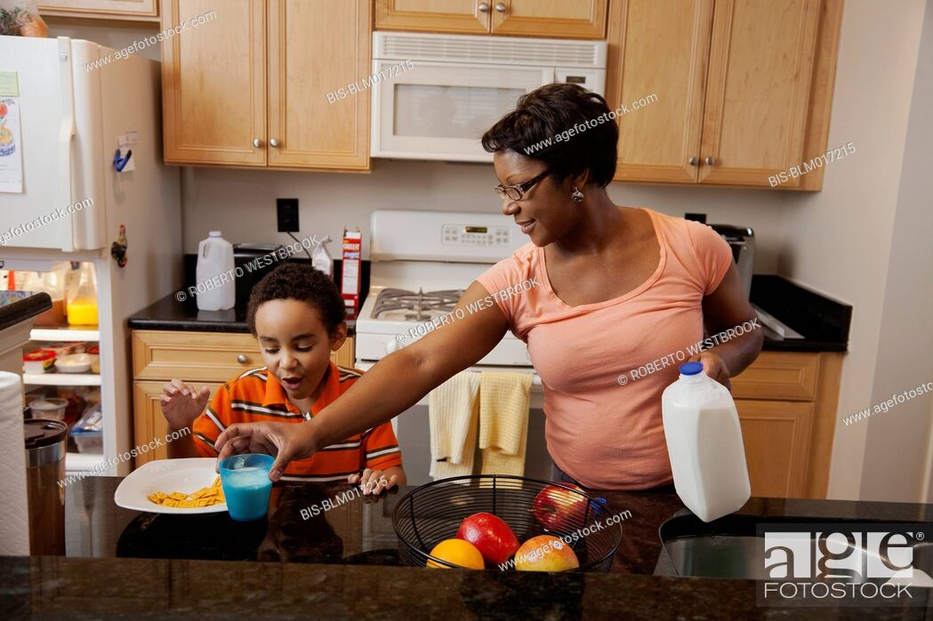 Imagen: Mother making lunch for son in kitchen.