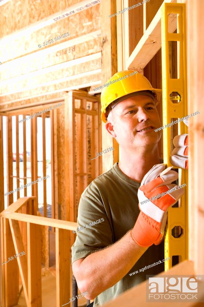Stock Photo: Builder in hardhat using spirit level.