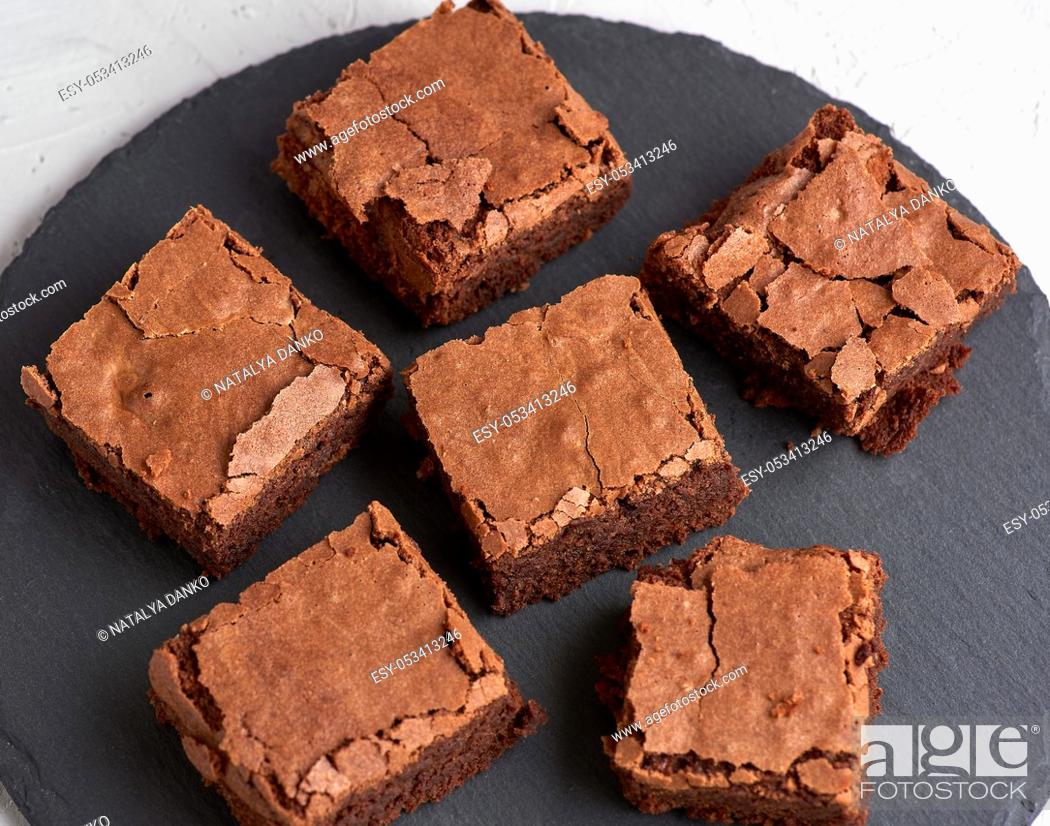 Stock Photo: pieces of chocolate brownie on a black round graphite plate, top view.