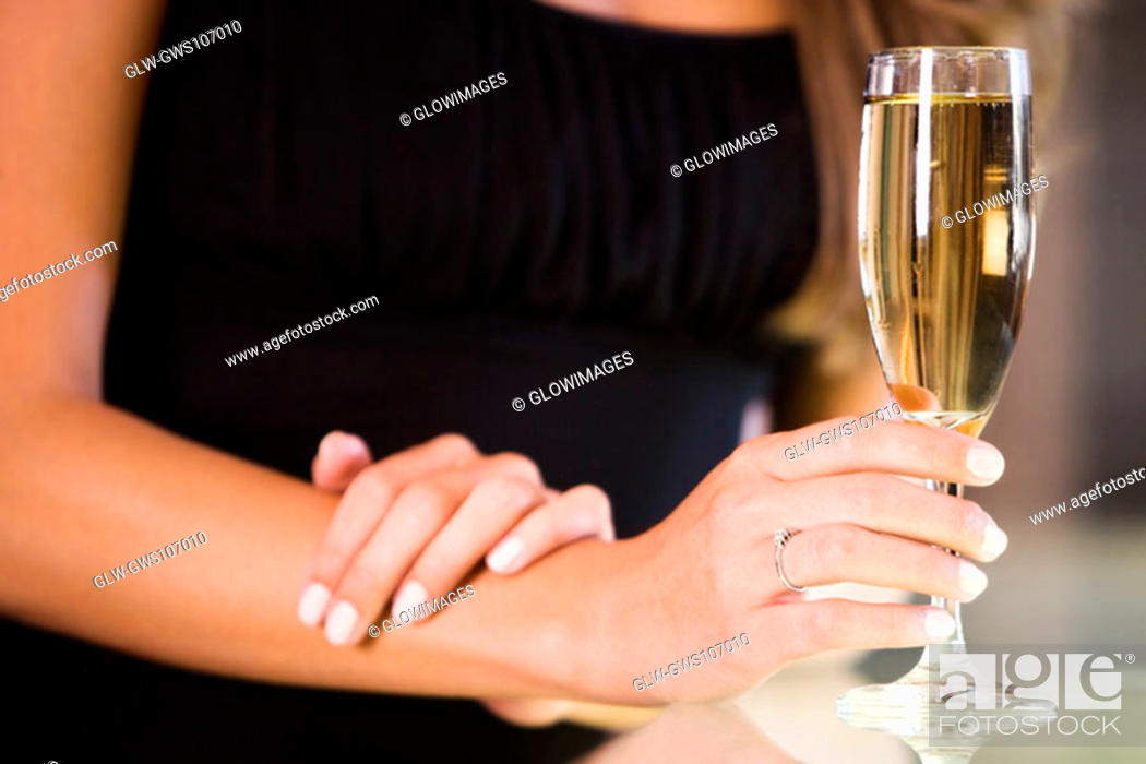 Stock Photo: Mid section view of a young woman holding a champagne flute.