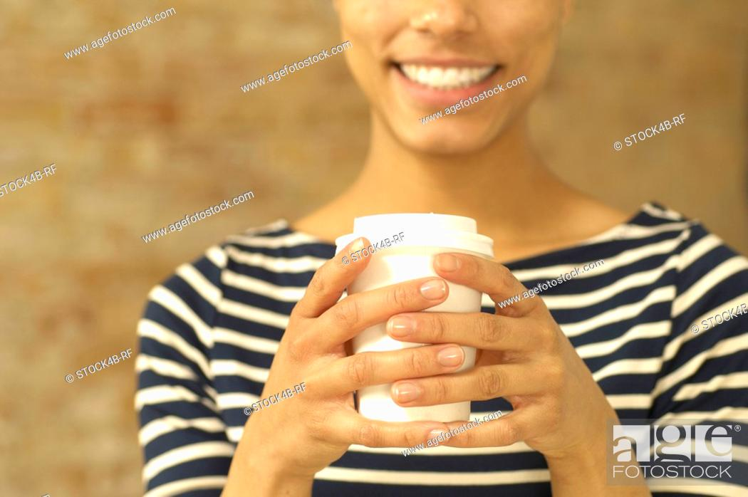 Stock Photo: Smiling young woman holding plastic cup.