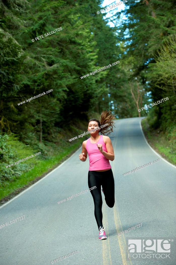 Stock Photo: Mixed race runner training on remote road.
