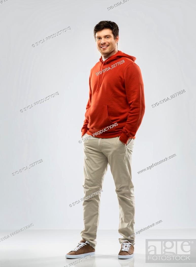 Stock Photo: young man in red hoodie over grey background.