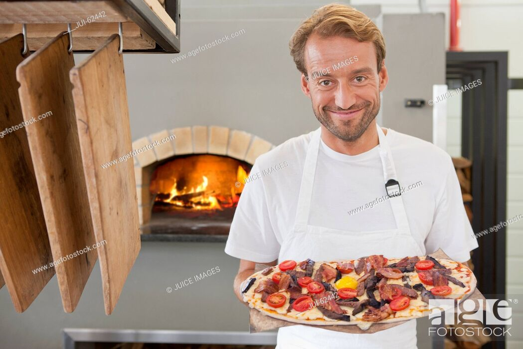 Stock Photo: Smiling chef holding pizza in kitchen.