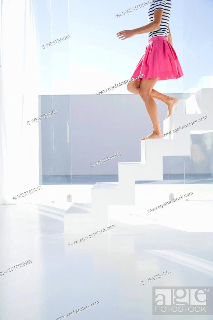 Stock Photo: Spain, Mid adult woman walking down stairway.