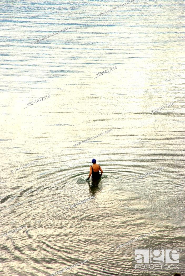 Stock Photo: Female swimmer wading out to sea in evening light.