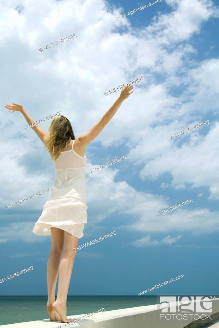 Stock Photo: Woman in sundress standing next to sea with arms raised, rear view.