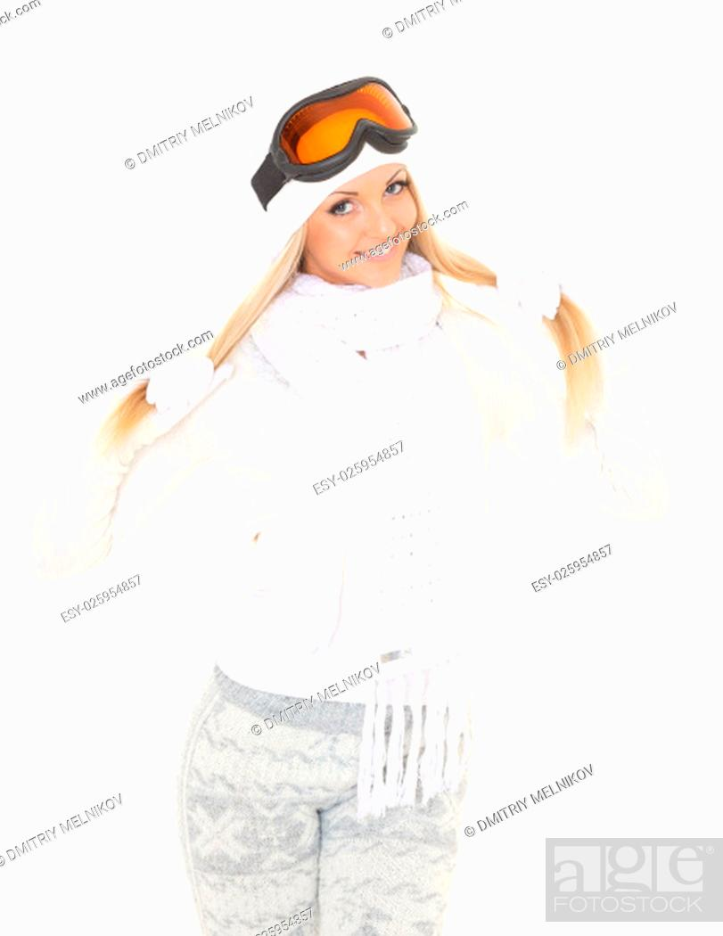 Stock Photo: Young happy woman in winter warm clothes and ski glasses stands on a white background. Winter sports.