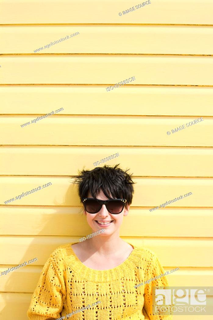 Stock Photo: Young woman and yellow wall.