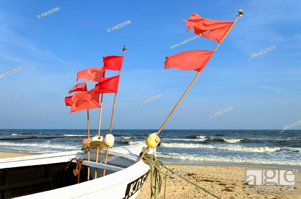 Fishing boat with red marker flags, on the beach, Usedom