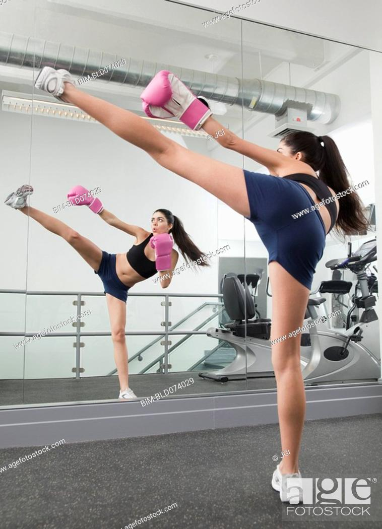 Stock Photo: Hispanic woman kick boxing in health club.