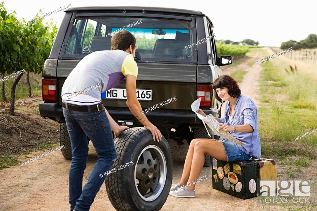 Stock Photo: Couple by suv with tyre and map.