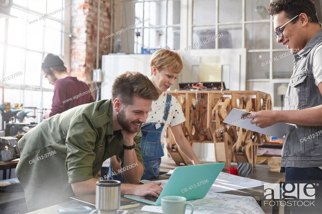 Stock Photo: Designers brainstorming at laptop in workshop.