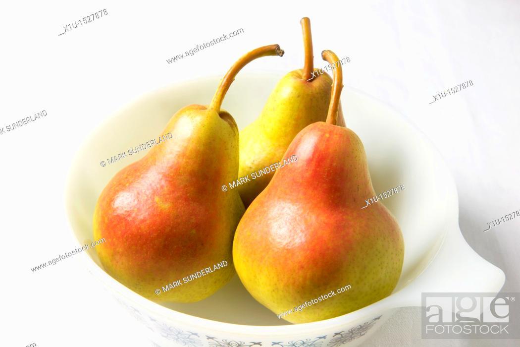 Stock Photo: Three blush pears in a white dish.