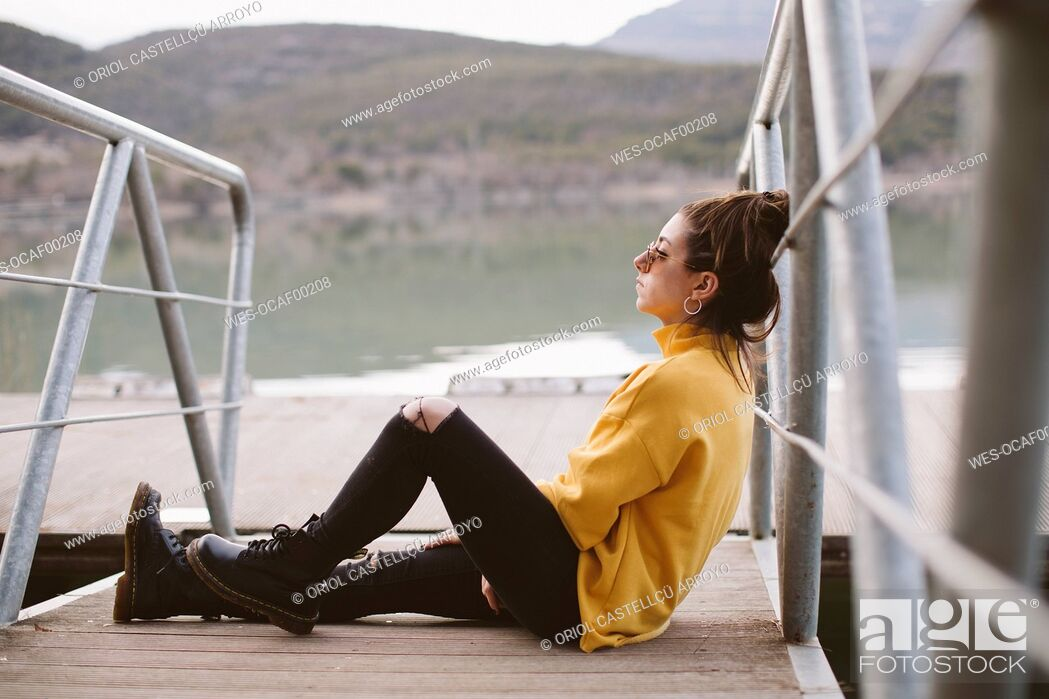 Stock Photo: Pensive young woman relaxing on jetty.